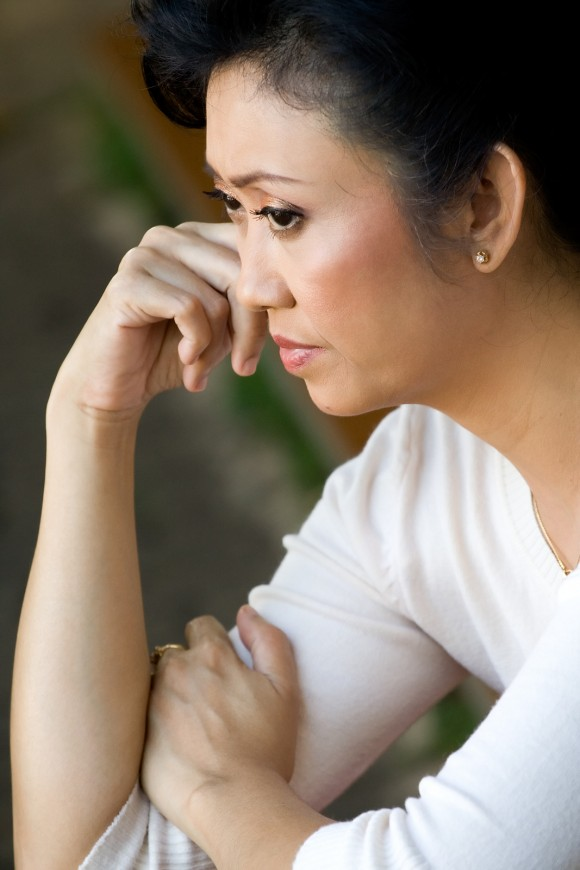 portrait of asian mature woman in sorrow having a seriuos tought of a problems